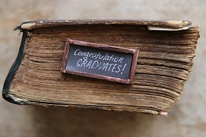 congratulations graduates text and vintage book on table