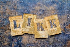 """Brass letters showing """"LIKE"""""""