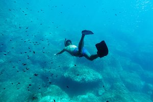 man swim underwater in snorkel