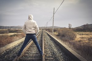 Young man standing on a railway