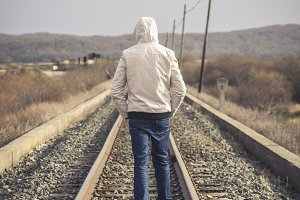 Young man walking on a railway