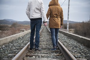 Young couple walking on a railway