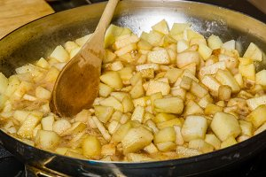 Fresh apples cut up being cooked into sauce