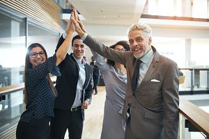 Positive business people giving high five in office