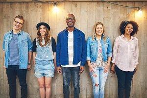 Cheerful multiracial company standing at wooden wall
