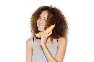 Young pretty woman making fun with banana