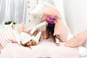 Two girls having fun in bedroom