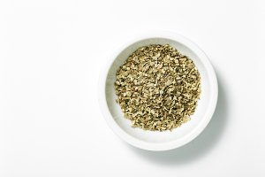 Bowl of dried oregano leaves isolated on white , top view