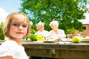 Little Girl And Her Grandparents Are Having A Picnic