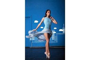 The modern ballet dancer posing on blue city background
