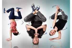 Break dancers doing handstand against white background