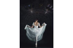 Portrait of the classical ballerina in white dress on black back