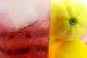 Glass with fruit soda near lemons