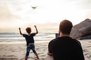 Father operating drone at beach