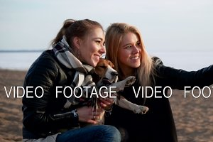 two beautiful young woman sisters make selfie photo using telephone camera with their active dog