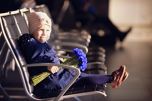Girl with flowers at the airport
