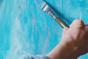 Hand of artist with paintbrush