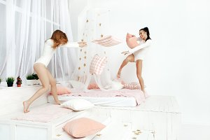 Young women fighting pillows in the bedroom