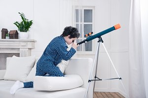 little boy looking through telescope