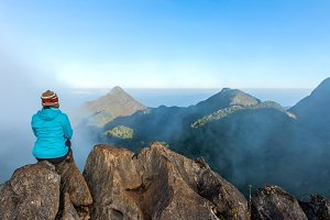 human on mountain sitting see view