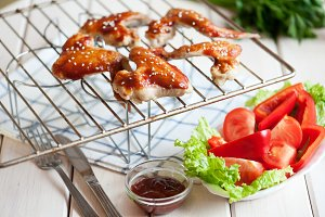 Hot spicy bbq chicken wings on grill with sauce