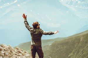 Happy Man jumping to mountains peaks