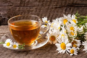 Herbal tea with fresh chamomile flowers on old wooden background