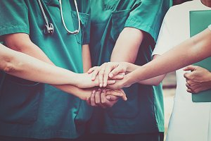 Doctors and nurses coordinate hands