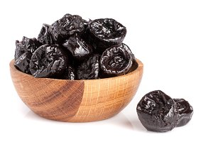 Dried plums or prunes in wooden bowl isolated on white background