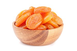 Dried apricots in a wooden bowl isolated on white background