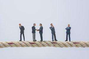 miniature people standing on a rope