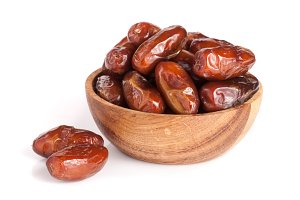 Dates in a wooden bowl isolated on white background