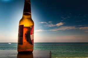 A bottle of beer,in front of the sea
