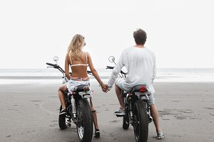 Young beautiful couple on motorcycles