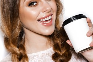Girl holding paper cup of coffee