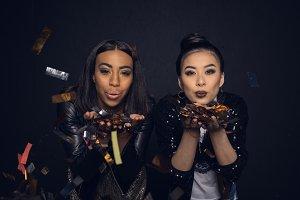 young women blowing shiny confetti