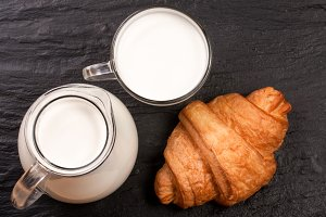Jug and a glass of milk with a croissant on a black stone background. Top view