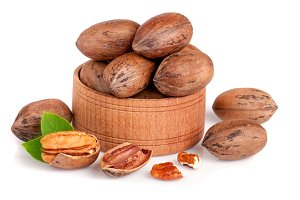 pecan in a wooden bowl with leaves isolated on white background