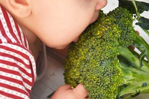 Child little girl eats vegetable. Little baby with broccoli. Baby with vegetables