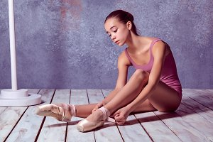 young ballerina putting on her ballet shoes.