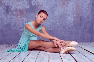 young ballerina sitting on wooden floor