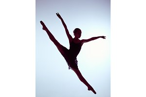 Beautiful young ballet dancer jumping on a gray background.