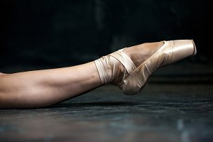 Close-up ballerina's leg in pointes on the black wooden floor