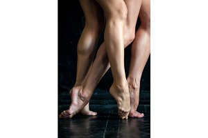 Close-up ballerina's legs on the black wooden floor