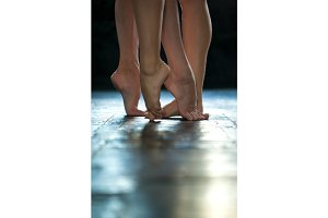 Close-up ballerina's legs on the wooden floor
