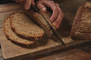 male chef's hand cutting Rye bread