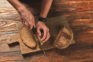Men's hands cut fresh bread