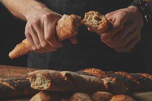 Male hands break the baguette