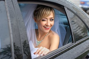 Brides smiles in the car