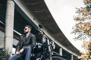 Man seat on the motorcycle on the city bridge